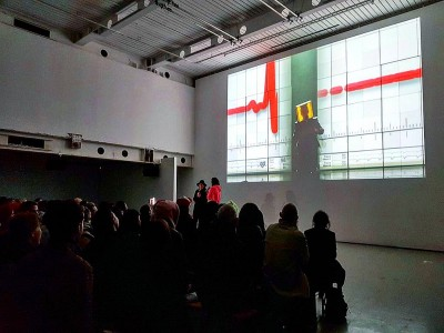 An audience look towards two figures stood in front of a projected image.