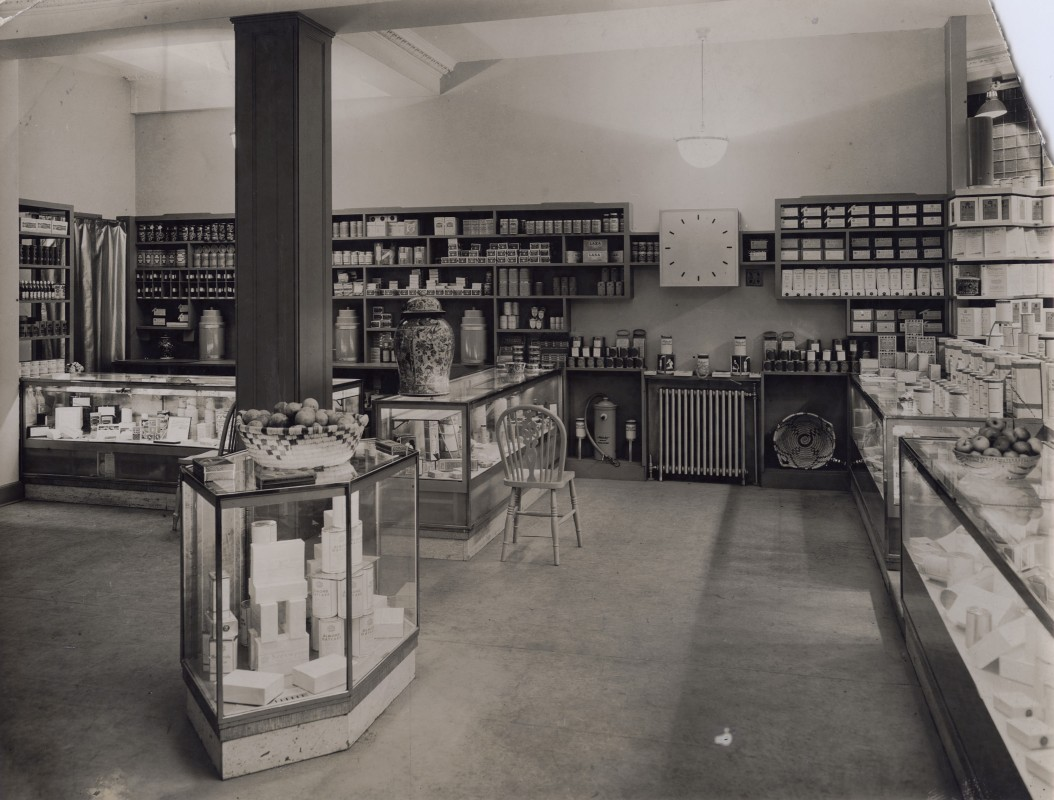 Black and white photograph of shop interior with display cabinets and shelves