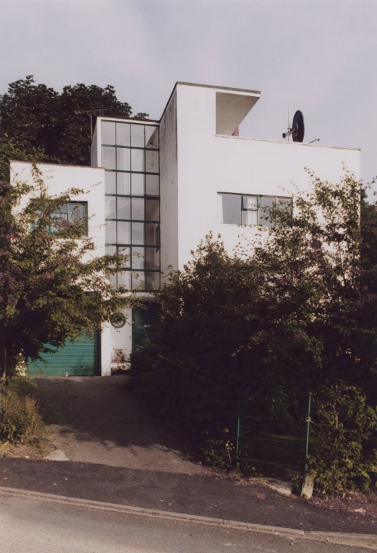 Photograph of white modern building with trees