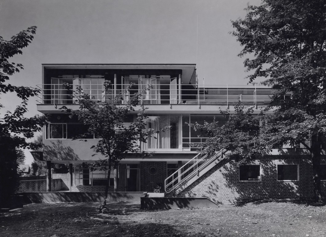 Black and white photograph of two storey modern building with trees