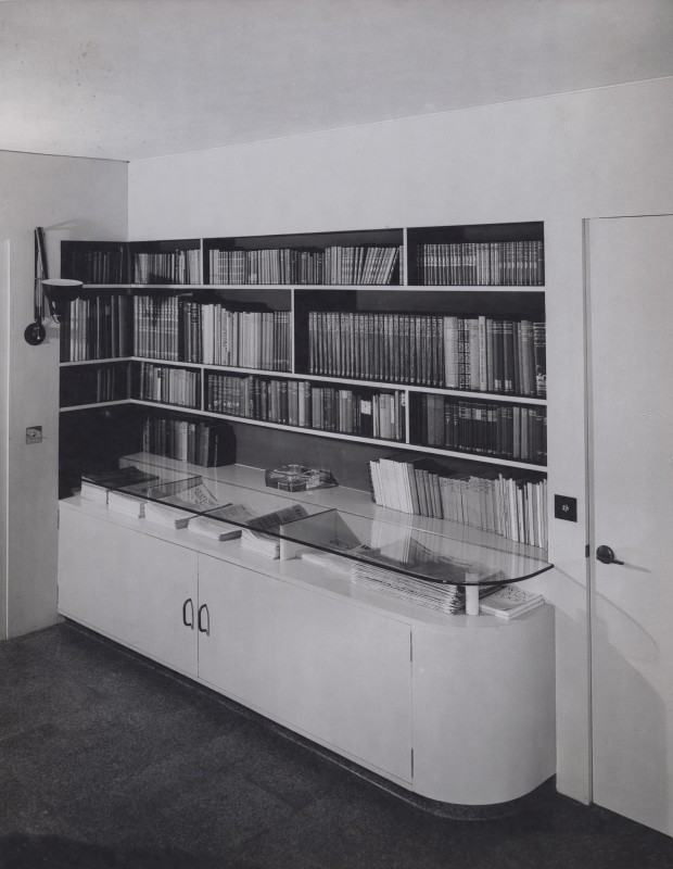 Black and white photograph of room interior showing book shelves and cabinet