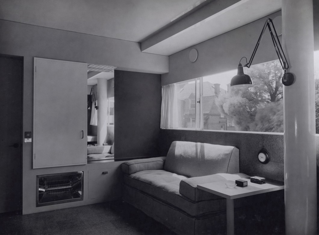 Black and white photograph of an interior with sofa and angle poise lamp