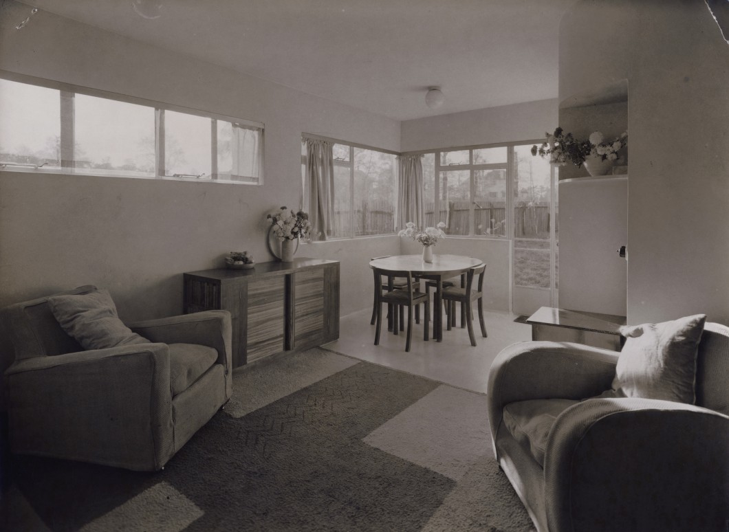 Black and white photograph of a living room interior with arm chairs