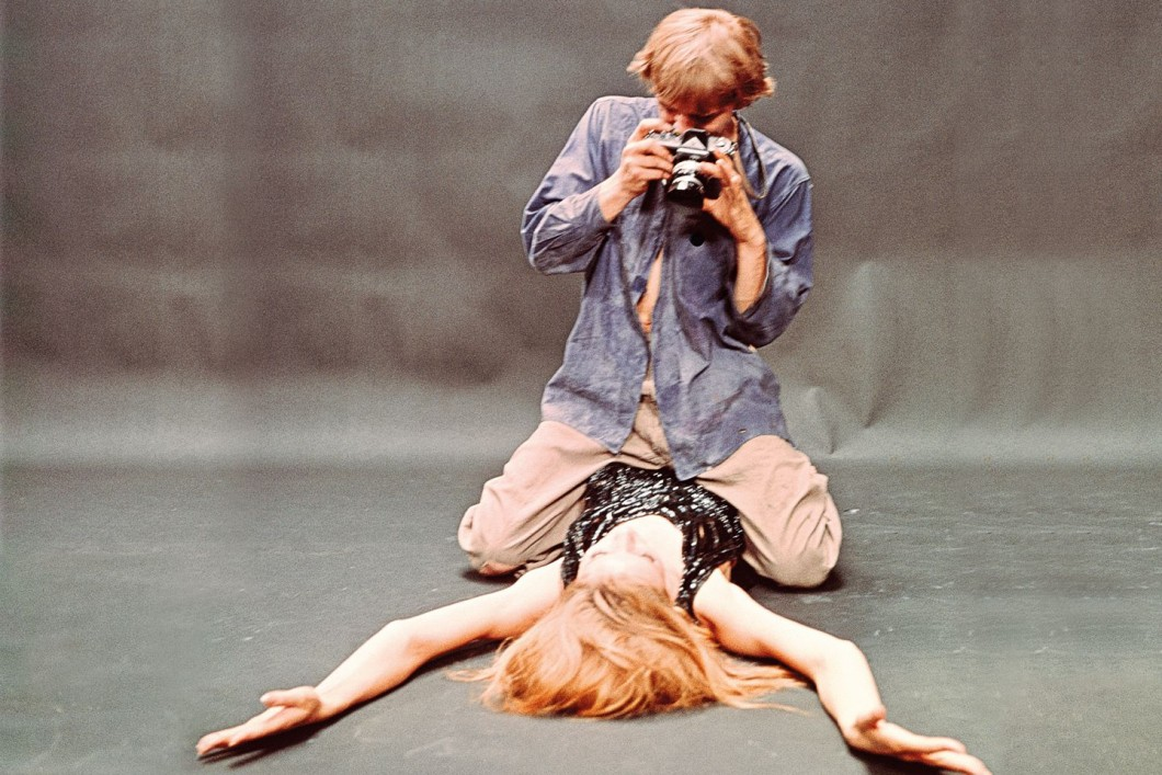 Photographer straddling model with out stretched arms