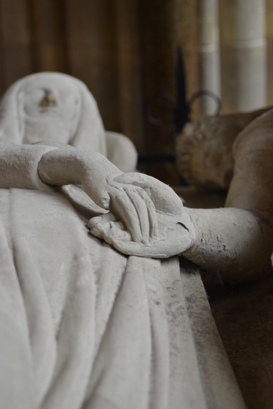 Sculpted figures laying down, hands clasped