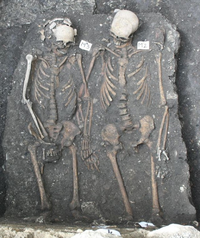 Skeletal remains in archaeological site holding hands