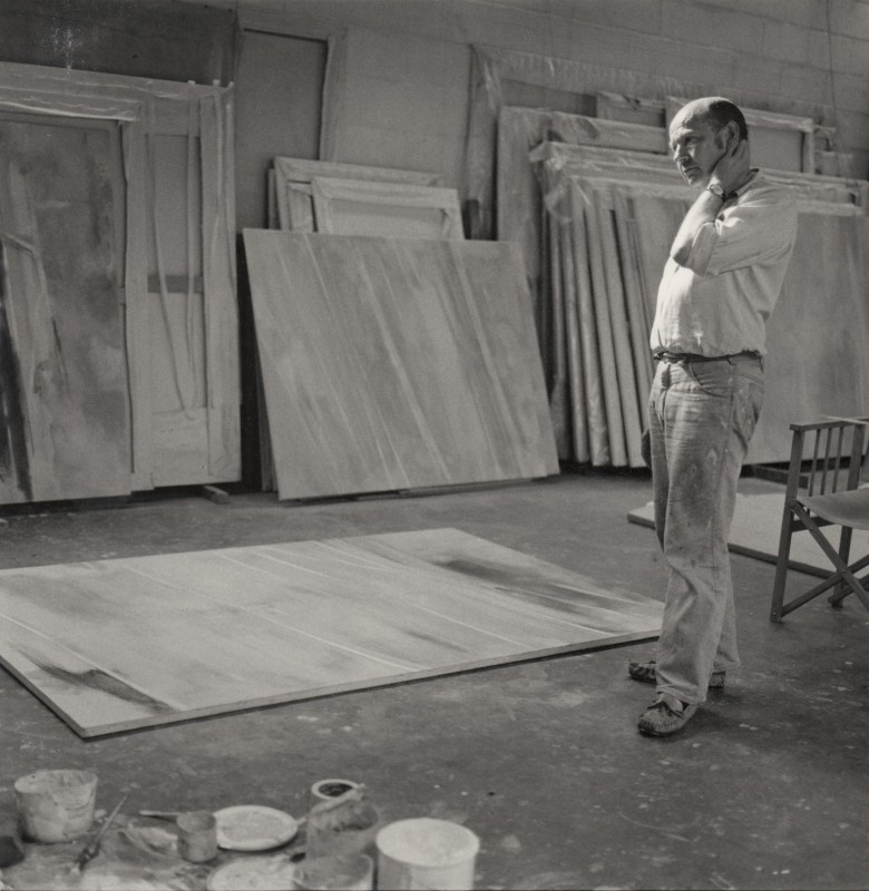 Black and white photograph of a man looking at a canvas on the floor