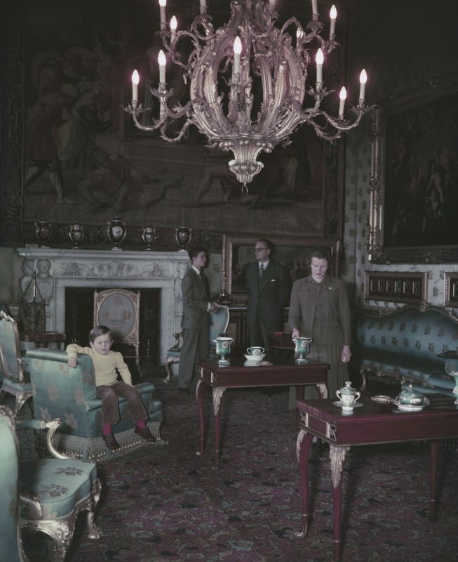 Photographic image of a man, woman, and two children within a stately interior.