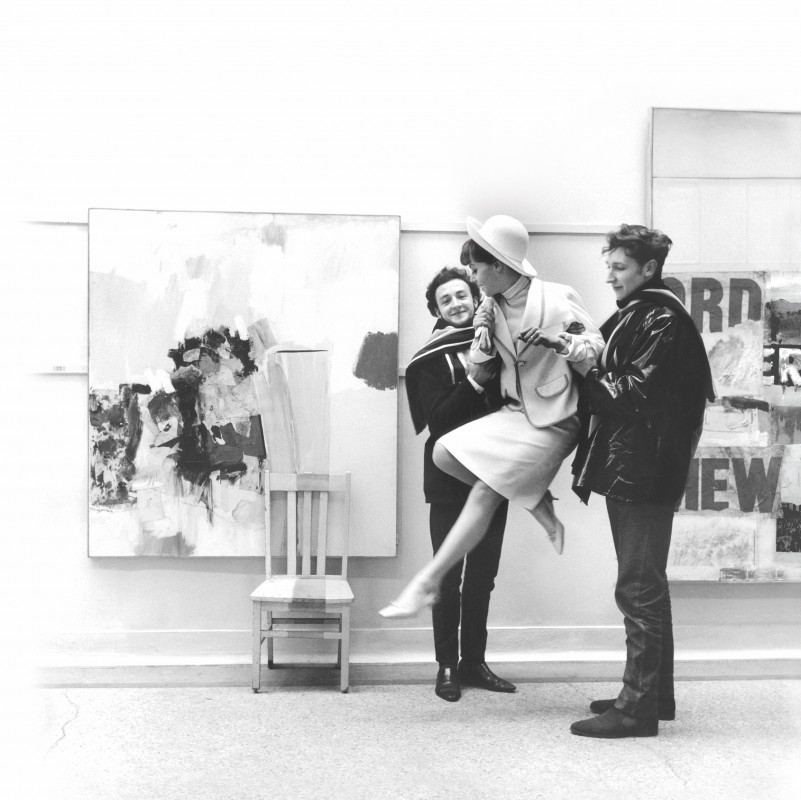 Woman in 1960s style skirt suit being lifted by two men in front of paintings