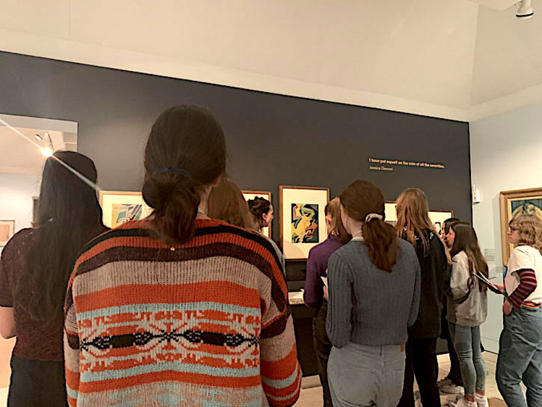 young people listening to a talk in front of paintings