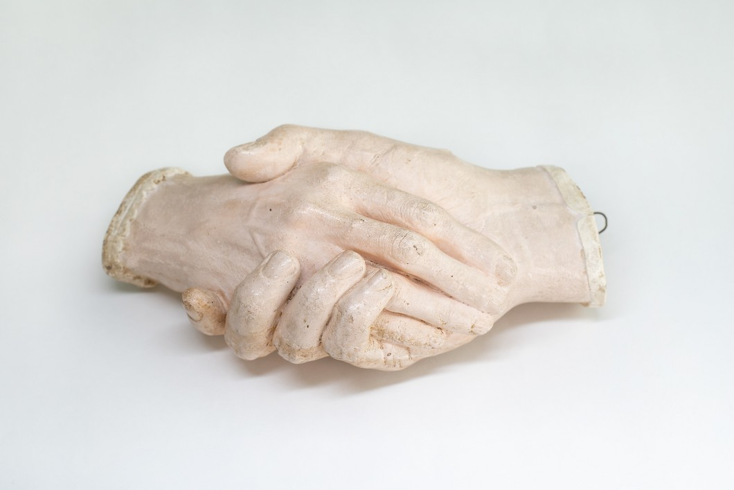 Life cast of two hands clasped together
