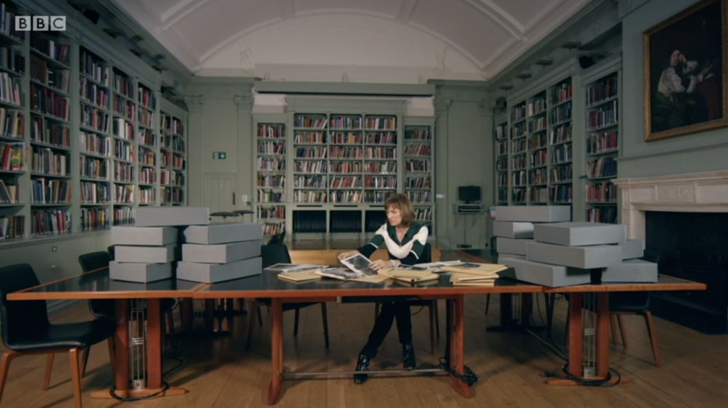 Fiona Bruce sitting at a table going through the archives in the Paul Mellon Centre Library