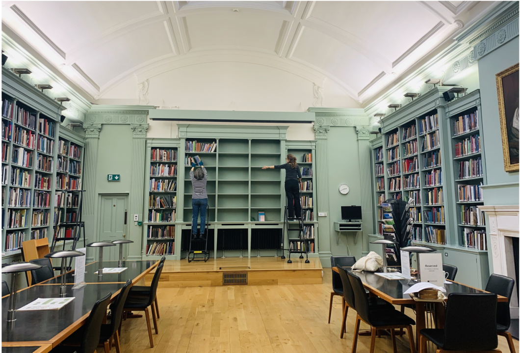 The Centre's library showing two staff members on ladders moving books.