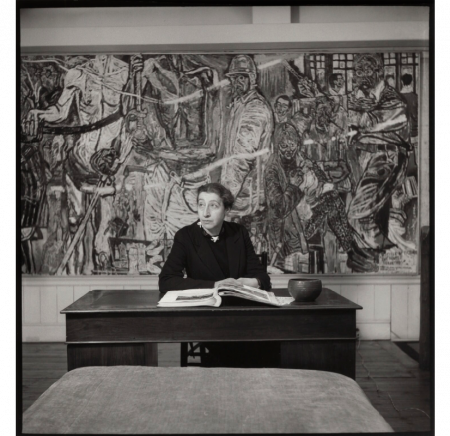 Black and white photograph of a woman sat at a desk in front of a painting.